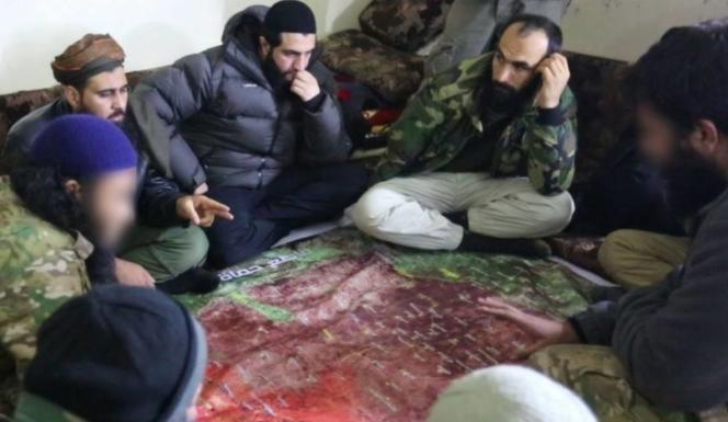 Une réunion des chefs jihadistes des divers groupes d'Idleb autour d'Abou Mohammed al-Joulani, émir de Hayat Tahrir al Cham.png